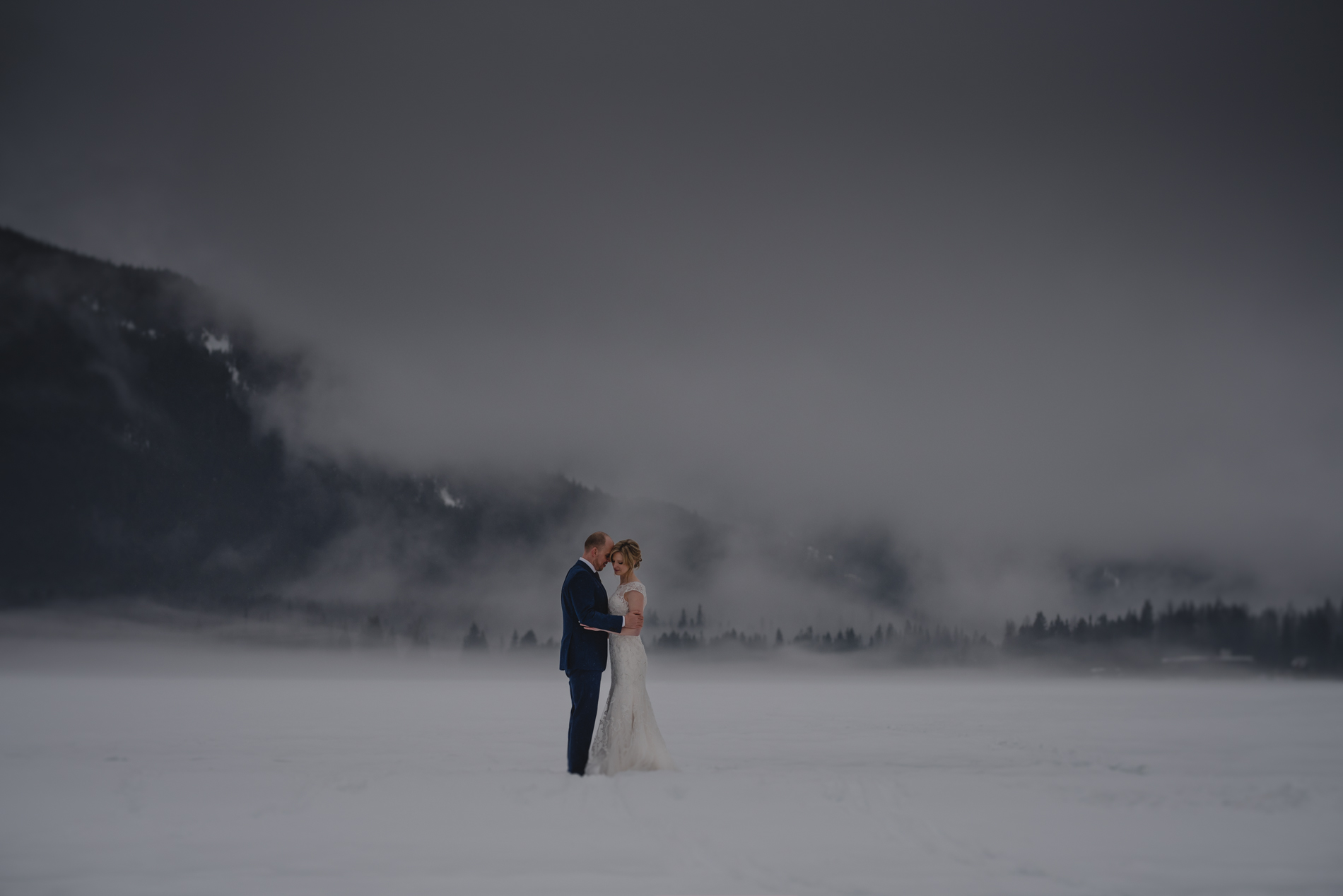 Wedding couple holding on a foggy frozen lake